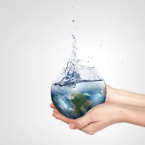 Globe in human hand against blue sky.